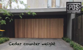 Counter weight garage door finished with cedar battens #counterweightgaragedoor #custommadegaragedoor #cedargaragedoor