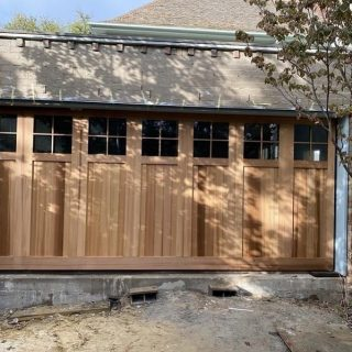 Tilt door finished with cedar and windows #custommadegaragedoor #tiltdoor